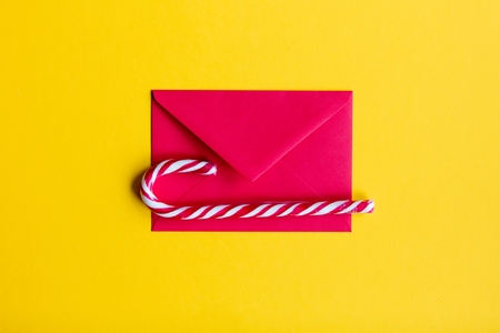lolipop: Red christmas envelope and lolipop on yellow background