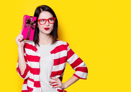 puntualidad: Retrato de una mujer joven en vidrios con caja de regalo sobre fondo amarillo