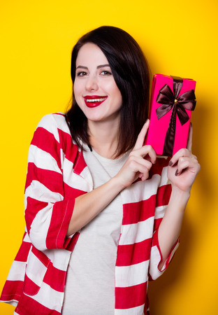 Portrait of a young woman with gift box on yellow background Stock Photo