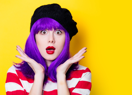 Portrait of a young woman with purple hair on yellow background Stock Photo
