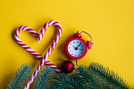 lolipop: christmas alarm clock  and lolipop on yellow background Stock Photo