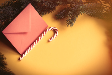 Red christmas envelope and lolipop on yellow background