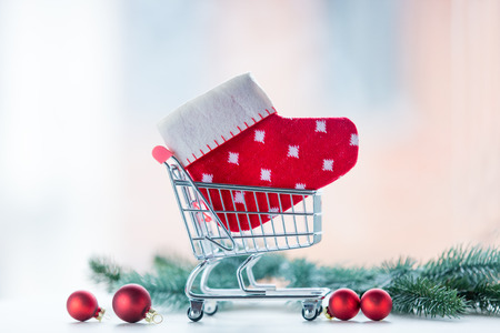 Christmas gift shopping cart and little sock with pine branch on background