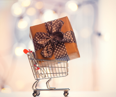 Christmas gift box and shopping cart on fairy lights background