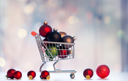 boxing day: Christmas decoration and shopping cart on fairy lights background Stock Photo