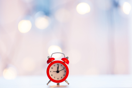 christmas alam clock with fairy lights on background Stock Photo