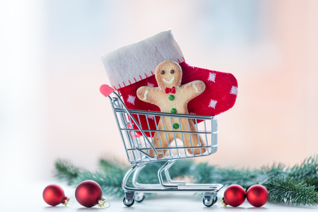 boxing day: Christmas cookie and sock in shopping cart with pine branch on background