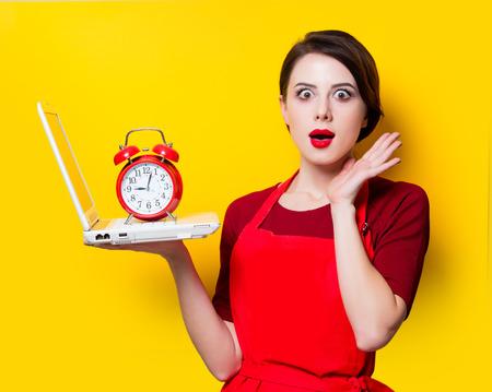 Portrait de jeune femme au foyer avec ordinateur portable et réveil sur fond jaune