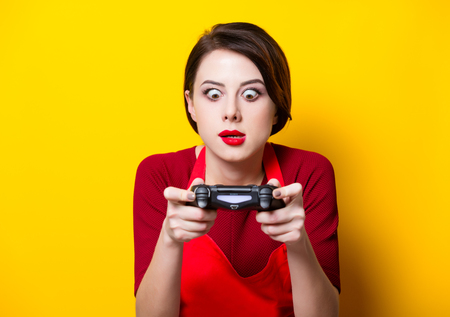 playstation: WROCLAW, POLAND - 20 december 2017: Young housewife with PlayStation 4 joystick on yellow background, Wroclaw, Poland