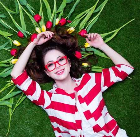 tulips in green grass: Portrait of a young styled redhead woman tulips around and glasses lying down on green spring grass, above point of view