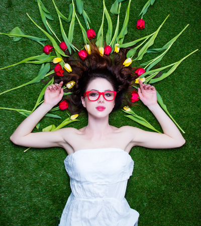 tulips in green grass: Portrait of a young redhead woman with tulips and glasses lying down on green spring grass, above point of view