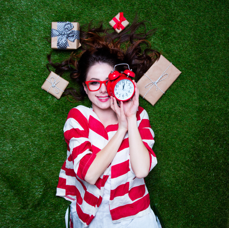 Portrait of a young styled redhead woman alarm clock and gifts around lying down on green spring grass, above point of view