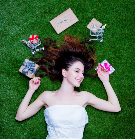 vestidos de epoca: Portrait of a young surprised redhead woman with holiday gifts and shopping carts lying down on green spring grass, above point of view