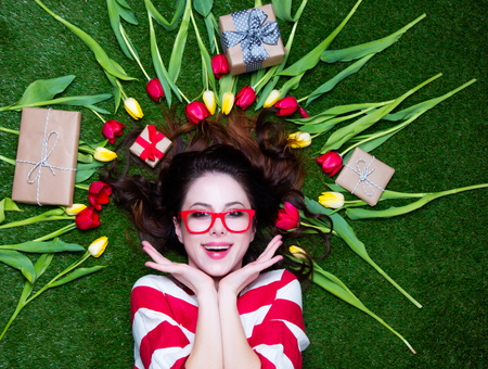 tulips in green grass: Portrait of a young styled redhead woman with tulips around and gift boxes lying down on green spring grass, above point of view