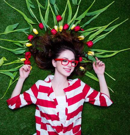 Portrait of a young styled redhead woman tulips around and glasses lying down on green spring grass, above point of view