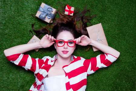 Portrait of a young redhead woman with present gifts lying down on green spring grass, above point of view Stock Photo