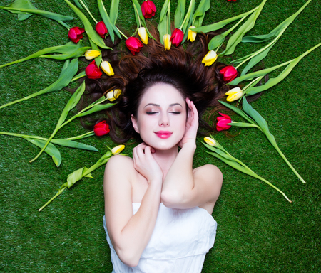 tulips in green grass: Portrait of a young redhead woman with tulips lying down on green spring grass, above point of view