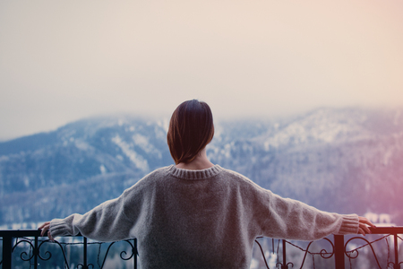 winter blues: Portrait of a young redhead woman with mountains on background Stock Photo