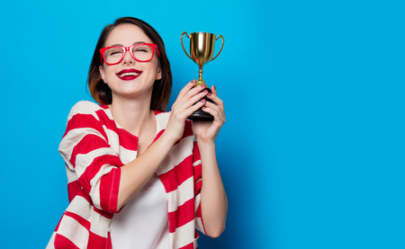 portrait of the beautiful young smiling woman with cup trophy on the blue background Stock Photo