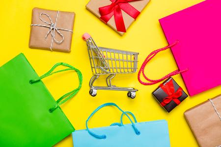 regali diversi, carrello della spesa e colorate borse della spesa sul meraviglioso sfondo giallo