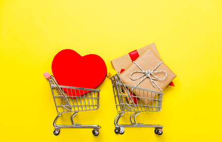 small gifts and heart shaped toy in the shopping carts on the beautiful yellow background Stock Photo
