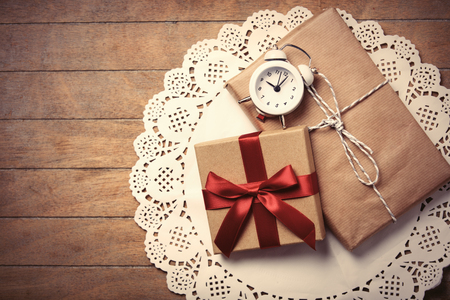 napkin ring: beautiful gifts and alarm clock on white napkin on the wonderful brown wooden background