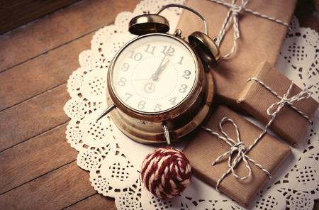 napkin ring: beautiful gifts, knitted ball and alarm clock on white napkin on the wonderful brown wooden background Stock Photo