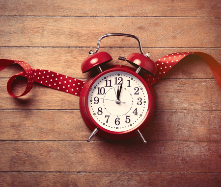 woderful: beautiful alarm clock and red ribbon lying on the woderful brown wooden background Stock Photo