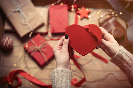 beautiful woman hands wrapping heart shaped toy on the wonderful decoration background
