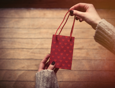 papel filtro: beautiful woman hands holding cute little red shopping bag on the wonderful brown wooden background