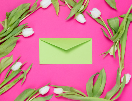 beautiful green envelope and tender white tulips lying on the wonderful pink background