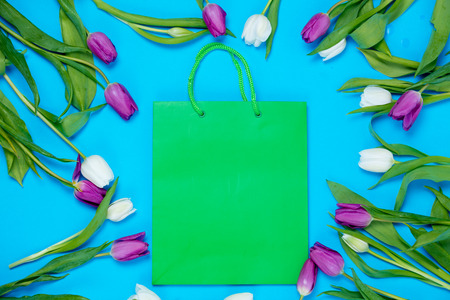 beautiful green shopping bag and tender white and purple tulips lying on the wonderful blue background