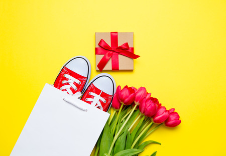bunch of red tulips, red gumshoes, cool shopping bag and beautiful gift on the wonderful yellow background Stock Photo