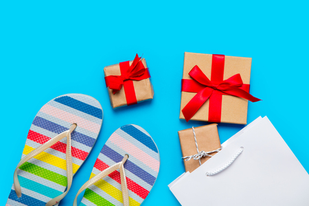 comprando zapatos: colorful sandals, shopping bag and beautiful gifts on the wonderful blue background