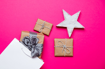 cute gifts, star shaped toy and shopping bag on the wonderful pink background Stock Photo