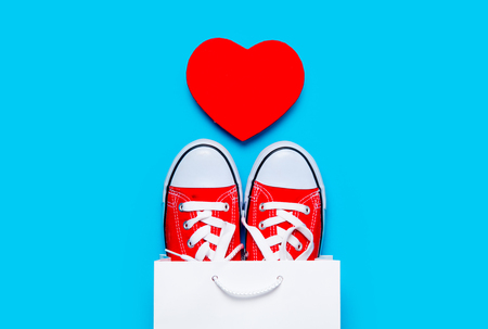 comprando zapatos: big red gumshoes in cool shopping bag and heart shaped toy on the wonderful blue background