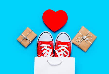 shoelace: big red gumshoes in cool shopping bag, heart shaped toy and beautiful gifts on the wonderful blue background