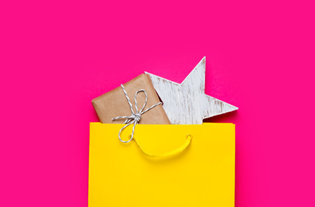 cute gift and star shaped toy in beautiful yellow shopping bag on wonderful pink background