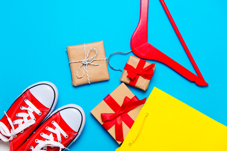 big red gumshoes, cool shopping bag, hanger and beautiful gifts on the wonderful blue background