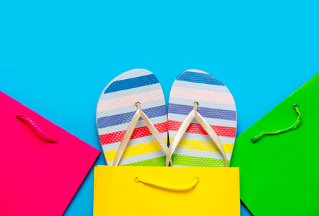 slippers: colorful sandals in cool shopping bag near other beautiful shopping bags on the wonderful blue background Stock Photo
