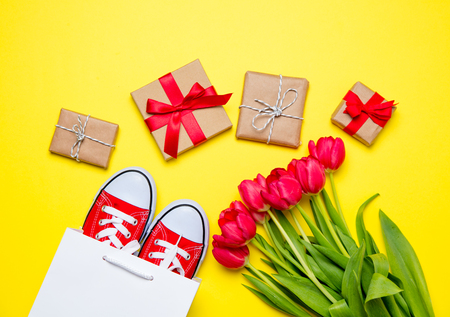 bunch of red tulips, red gumshoes, cool shopping bag and beautiful gifts on the wonderful yellow background Stock Photo