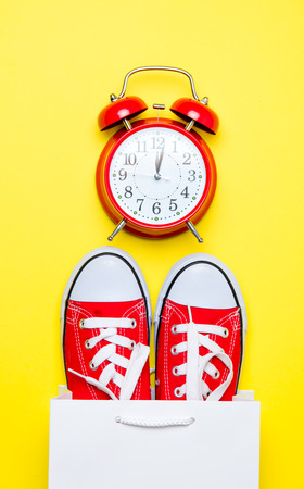 big red gumshoes in cool shopping bag and cute alarm clock on the wonderful yellow background Stock Photo