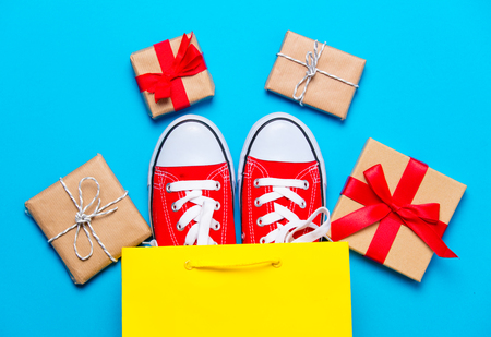 big red gumshoes in cool shopping bag and beautiful gifts on the wonderful blue background Stock Photo