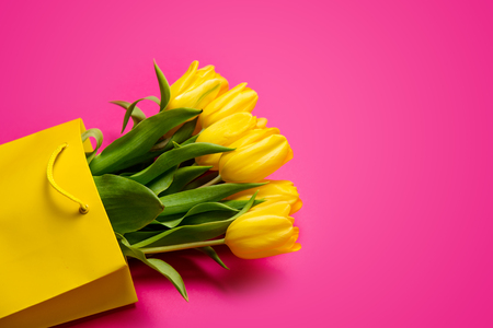 bunch of beautiful yellow tulips in cool yellow shopping bag on the wonderful pink background Stock Photo