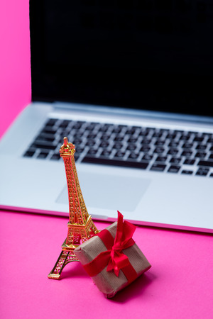 silver screen: beautiful eiffel tower shaped toy, small gift and cool laptop on wonderful pink background