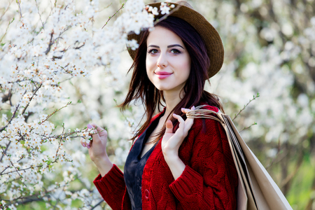 beautiful young woman with shopping bags standing in front of wonderful blooming trees background Stock Photo
