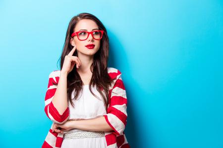 素晴らしい青い背景の前で眼鏡立っている美しい若い女性 写真素材