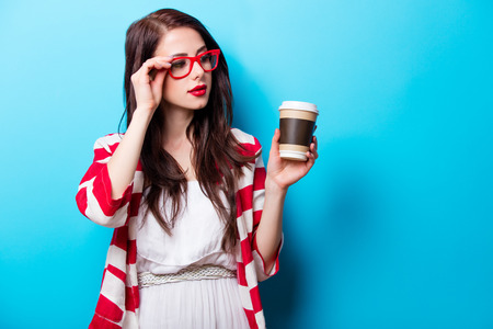 beautiful young woman with cup of coffee standing in front of wonderful blue background Stock Photo
