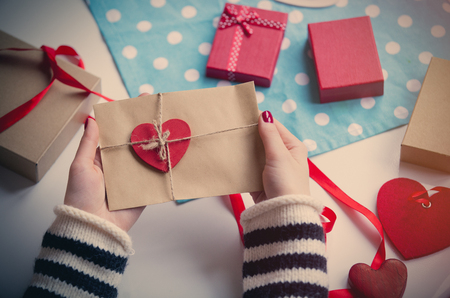 white caucasian hands holding heart shaped toy and envelope  on the wonderful things for decoration background