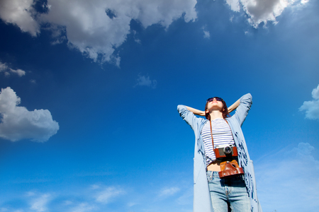 beautiful young woman with her retro camera onthe wonderful sky background